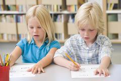 Two students in class learning letters Stock Photos