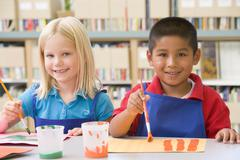 Two students in art class painting - stock photo