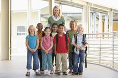 Stock Photo of Seven students standing with teacher outdoors at school