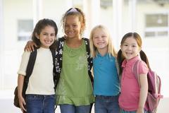 Neljä opiskelijaa koulun ulkopuolella pysyvän yhdessä hymyilee (suuri avain) Kuvituskuvat