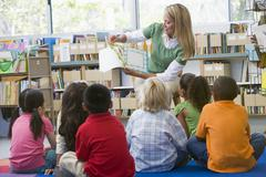 Teacher in class reading to students Stock Photos