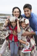 family on beach with blankets - stock photo