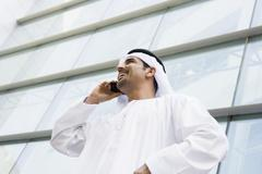 Businessman standing outdoors by building on cellular phone smiling (selective - stock photo