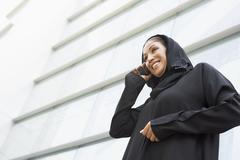 Businesswoman outdoors by building using cellular phone and smiling (selective - stock photo