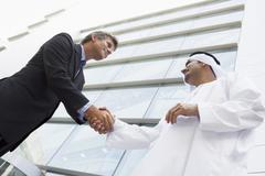 Two businessmen outdoors by building shaking hands and smiling (high Stock Photos