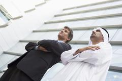 Two businessmen standing outdoors by building (high key/selective focus) - stock photo