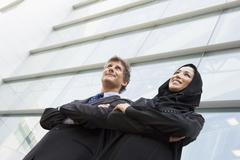 Two businesspeople standing outdoors by building smiling (selective focus) - stock photo
