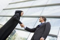 Two businesspeople standing outdoors by building shaking hands and smiling Stock Photos