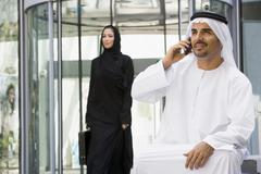 Businessman sitting outdoors by building using cellular phone with businesswoman - stock photo