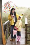 mother and daughter with umbrella - stock photo