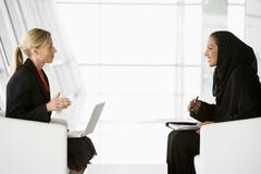 Two businesswomen indoors with a laptop talking and smiling (high key/selective - stock photo