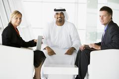 Three businesspeople indoors with a laptop smiling (high key/selective focus) - stock photo