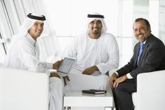 Three businessmen indoors with a laptop smiling (high key/selective focus) - stock photo