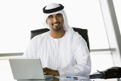Businessman in office with laptop smiling (high key/selective focus) - stock photo