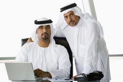 Two businessmen in office with laptop (high key/selective focus) Stock Photos