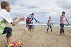 teenagers playing baseball on beach - stock photo