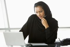 Businesswoman in office with laptop thinking (high key/selective focus) - stock photo