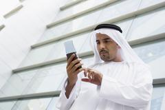 Businessman outdoors by building using PDA Stock Photos