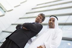 Two businessman standing outdoors by building smiling (high key/selective focus) Stock Photos