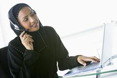 Woman wearing headset with laptop smiling (high key/selective focus) - stock photo