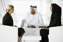 Three businesspeople indoors with laptop talking and smiling (high key/selective Stock Photos