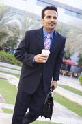 Businessman walking outdoors with coffee smiling (high key/selective focus) - stock photo