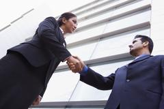 Two businesspeople outdoors by building shaking hands (high key/selective focus) - stock photo