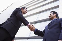 Two businessmen outdoors by building shaking hands and smiling (high - stock photo