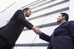 Two businessmen outdoors by building shaking hands (high key/selective focus) - stock photo