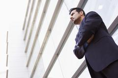 Businessman standing outdoors by building (high key/selective focus) - stock photo
