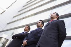 Three businessmen standing outdoors by building (high key/selective focus) - stock photo