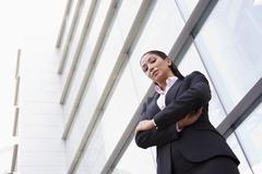 Businesswoman standing outdoors by building (high key/selective focus) Stock Photos