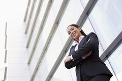 Businesswoman standing outdoors by building smiling (high key/selective focus) - stock photo