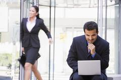 Businessman outdoors in front of building using laptop with businesswoman in Stock Photos