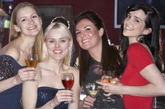 young women drinking at bar - stock photo
