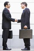 Two businessmen shaking hands outdoors holding briefcases and smiling - stock photo