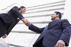 Two businesspeople outdoors by building shaking hands and smiling (high Stock Photos