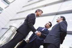 Three businessmen outdoors by building shaking hands and smiling (high - stock photo