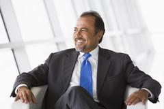 Businessman sitting indoors looking out window smiling (high key/selective - stock photo