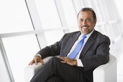 Businessman sitting indoors smiling (high key/selective focus) - stock photo
