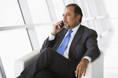 Businessman sitting indoors on cellular phone (high key/selective focus) - stock photo