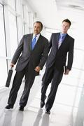 Two businessmen walking in a corridor (high key/selective focus) Stock Photos
