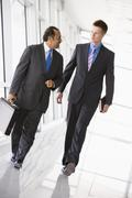 Two businessmen walking in a corridor talking (high key/selective focus) - stock photo