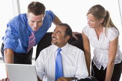 Three businesspeople in office with laptop talking and smiling (high Stock Photos