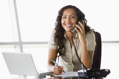 Businesswoman in office on telephone by laptop smiling (high key/selective - stock photo