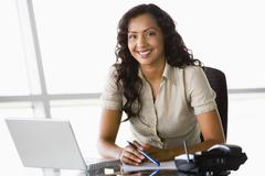 Businesswoman in office with laptop smiling (high key/selective focus) Stock Photos