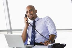 Businessman in office on telephone by laptop smiling (high key/selective focus) Stock Photos