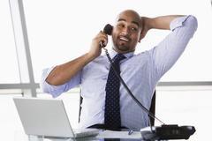 Businessman in office on telephone by laptop smiling (high key/selective focus) - stock photo