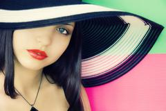 face of  young beautiful brunette in a summer hat - stock photo