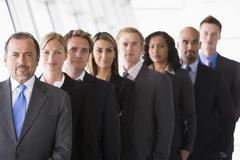 Group of co-workers standing in office space smiling (high key/depth of field) - stock photo